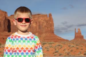 boy wearing sunglasses and rainb