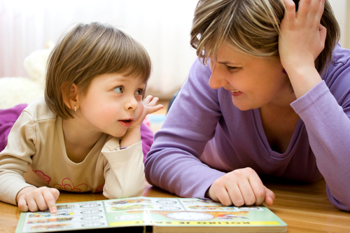 A child reads with her mother