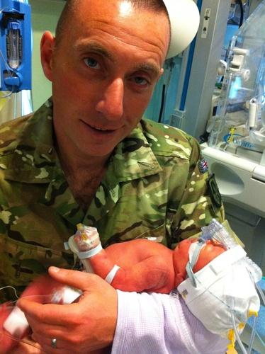 A proud dad cradles his CMV baby