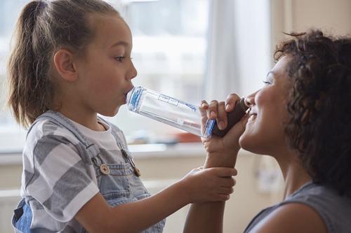 Mother helping daughter with inhaler