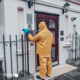 Man in PPE disinfecting touch plates